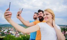 Todays selfie. Pretty woman and men holding smartphones in hands. People enjoy selfie shooting on natural landscape. Todays selfie. Pretty women and men holding royalty free stock image