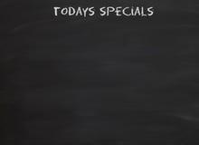 Todays specials on blackboard. Handwritten title todays specials on blackboard or chalkboard Royalty Free Stock Photos