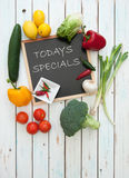 Todays specials menu. Specials menu board surrounded by fresh products Stock Images