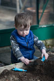 Todder playing in the garden. Young preschool boy digging in the garden soil royalty free stock photo