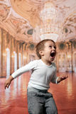 Toddler boy jumping. Toddle boy jumping in a large ballroom Royalty Free Stock Photography