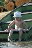 Toddle by the river. Little boy sitting on the rowboat by the river Royalty Free Stock Photos