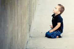 Toddler. A toddler sitting looking up at a cement wall Stock Image