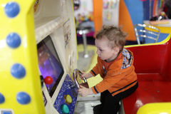 Toddler and amusement machine Stock Images