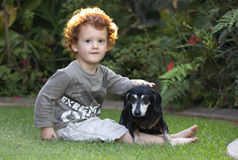 Toddler And Dog Sitting In Garden