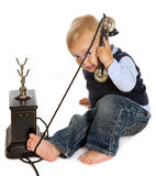 Toddler with antique telephone. Blonde toddler boy playing with a black antique telephone Stock Images