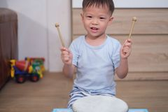 Toddler baby boy child hold sticks & plays a musical instrument drum. Cute happy smiling little Asian 2 - 3 years old toddler baby boy child hold sticks & plays stock images