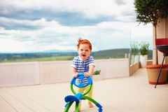 A toddler baby boy pushing go cart, outdoors. Happy toddler baby boy pushing pushing go cart, outdoors Royalty Free Stock Photo