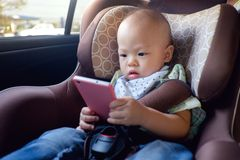 Toddler baby boy sitting in car seat and watching a video from smart phone stock photo