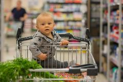 Toddler baby boy, sitting in a shopping cart in grocery store, s. Miling and eating bread  while mommy is shopping Stock Photography