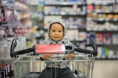 Toddler baby boy, sitting in a shopping cart in grocery store, s. Miling and eating bread  while mommy is shopping Royalty Free Stock Images