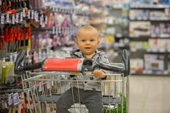 Toddler baby boy, sitting in a shopping cart in grocery store, s. Miling and eating bread  while mommy is shopping Stock Photo