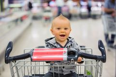 Toddler baby boy, sitting in a shopping cart in grocery store, s. Miling and eating bread  while mommy is shopping Royalty Free Stock Photography