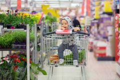 Toddler baby boy, sitting in a shopping cart in grocery store, s. Miling and eating bread  while mommy is shopping Stock Images