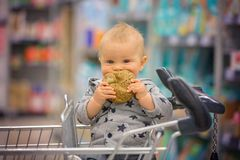 Toddler baby boy, sitting in a shopping cart in grocery store, s. Miling and eating bread while mommy is shopping royalty free stock photo