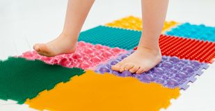 Toddler on baby foot massage mat. Exercises for legs on orthopedic massage carpet. prevention of flat feet and hallux valgus. Toddler baby foot massage mat stock image
