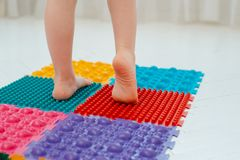 Toddler on baby foot massage mat. Exercises for legs on orthopedic massage carpet. prevention of flat feet and hallux valgus. Toddler baby foot massage mat royalty free stock image