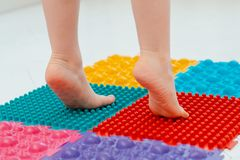 Toddler on baby foot massage mat. Exercises for legs on orthopedic massage carpet. prevention of flat feet and hallux valgus. Toddler baby foot massage mat stock images