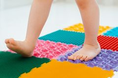 Toddler on baby foot massage mat. Exercises for legs on orthopedic massage carpet. prevention of flat feet and hallux valgus. Toddler baby foot massage mat royalty free stock photography