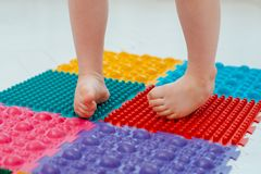 Toddler on baby foot massage mat. Exercises for legs on orthopedic massage carpet. prevention of flat feet and hallux valgus. Toddler baby foot massage mat royalty free stock photo