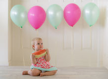 Toddler baby girl eating watermelon. Young girl eating watermelon with balloons in background wearing watermelon dress. Space for copy Stock Photos