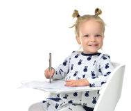 Toddler baby girl learning how to write on a paper book with pen. Happy smiling laughing isolated on white background royalty free stock images