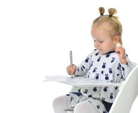 Toddler baby girl learning how to write on a paper book with pen Stock Photo
