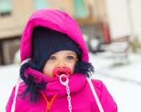 Toddler baby girl in a magenta snow suit playing on the snow. Stock Photo