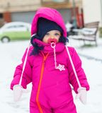 Toddler baby girl in a magenta snow suit playing on the snow. Stock Photography