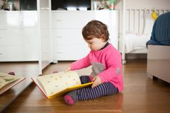 Toddler baby girl playing with fairy tales book. On the oak wood floor Stock Image