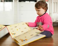 Toddler baby girl playing with fairy tales book. On the oak wood floor royalty free stock photography
