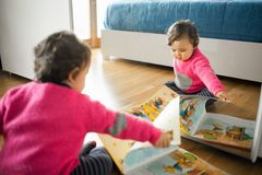 Toddler baby girl playing with fairy tales book. On the oak wood floor Stock Photography