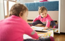 Toddler baby girl playing with fairy tales book. On the oak wood floor Royalty Free Stock Photo