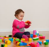 Toddler baby girl playing with rubber building blocks. Toddler baby girl plays with soft rubber building blocks royalty free stock image