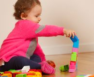 Toddler baby girl playing with rubber building blocks. Toddler baby girl plays with soft rubber building blocks stock images
