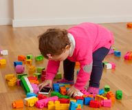 Toddler baby girl playing with smart phone between the toys Stock Image