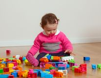 Toddler baby girl playing with rubber building blocks. Toddler baby girl plays with soft rubber building blocks royalty free stock photo