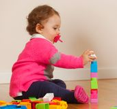 Toddler baby girl playing with rubber building blocks. Toddler baby girl plays with soft rubber building blocks stock photo