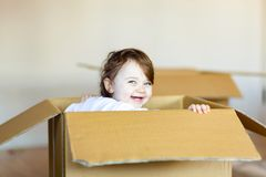 Toddler baby girl sitting inside brown cardboard box. Royalty Free Stock Photo