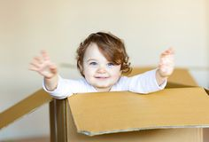 Toddler baby girl sitting inside brown cardboard box. Royalty Free Stock Image