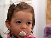 Toddler baby girl using a pacifier dummy Stock Images