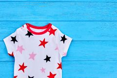 Toddler baby natural cotton clothes. Infant baby corron t-shirt on blue background. Kids summer clothing royalty free stock photos