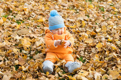 Toddler baby playing in autumn park Stock Photos