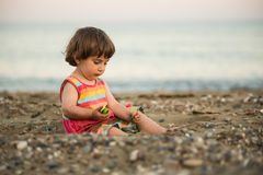 Toddler baby playing on a beach Stock Photo