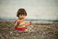 Toddler baby playing on a beach Stock Image