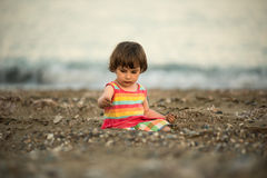 Toddler baby playing on a beach Stock Photos