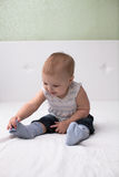 Toddler baby pulls socks, independence, childhood, home, light Royalty Free Stock Photography