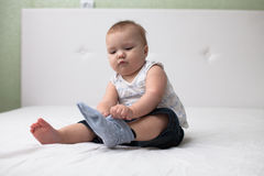 Toddler baby pulls socks, independence, childhood, home, light Stock Image
