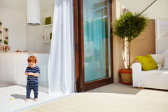 A toddler baby walking on open space kitchen with roof top patio and sliding doors. A toddler baby boy walking on open space kitchen with roof top patio and stock photography