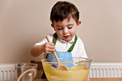 Toddler Baking. Happy young boy baking in the kitchen royalty free stock images